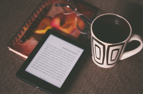 An e-reader resting on a notebook next to a pair of glasses and a cup of coffee