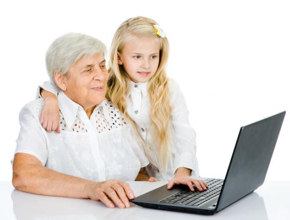 Woman in her seventies is using a laptop computer. Her young granddaughter has one arm around her and is looking at the laptop screen
