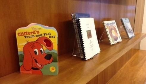 oak bookshelf holding the children's book Clifford's Touch and Feel Day