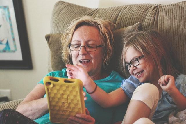 Grandmother and grandchild looking at a tablet