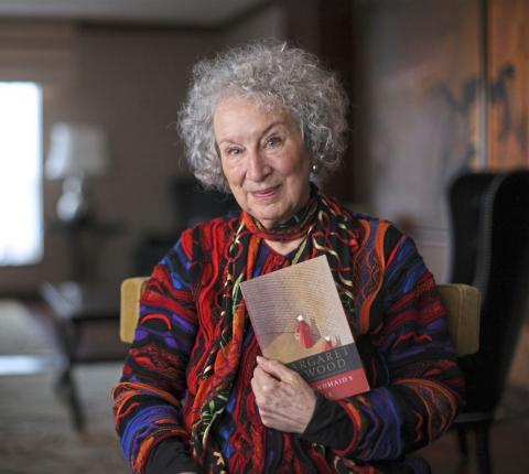 Photo of Margaret Atwood holding a copy of The handmaid's tale