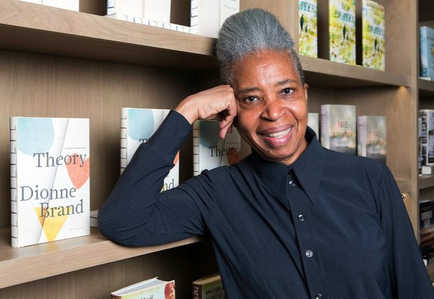 Photo of Dionne Brand standing next to a copy of Theory