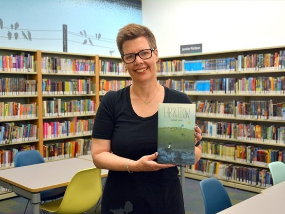 Picture of author holding their book Ebb and flow