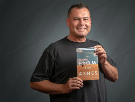 Photo of author holding a copy of his book From the ashes
