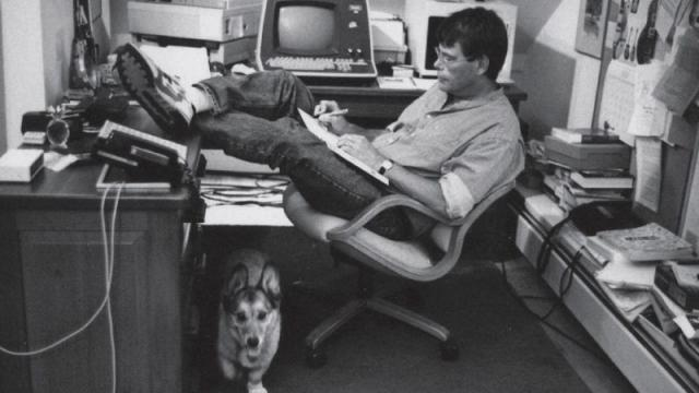 Photograph of Stephen King in his office reading