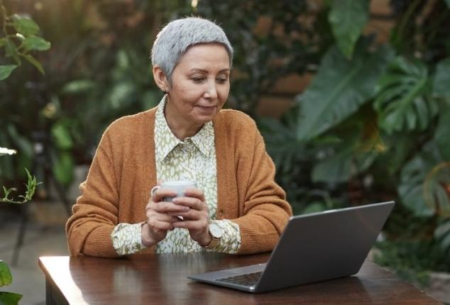 elderly woman smiling and using computer